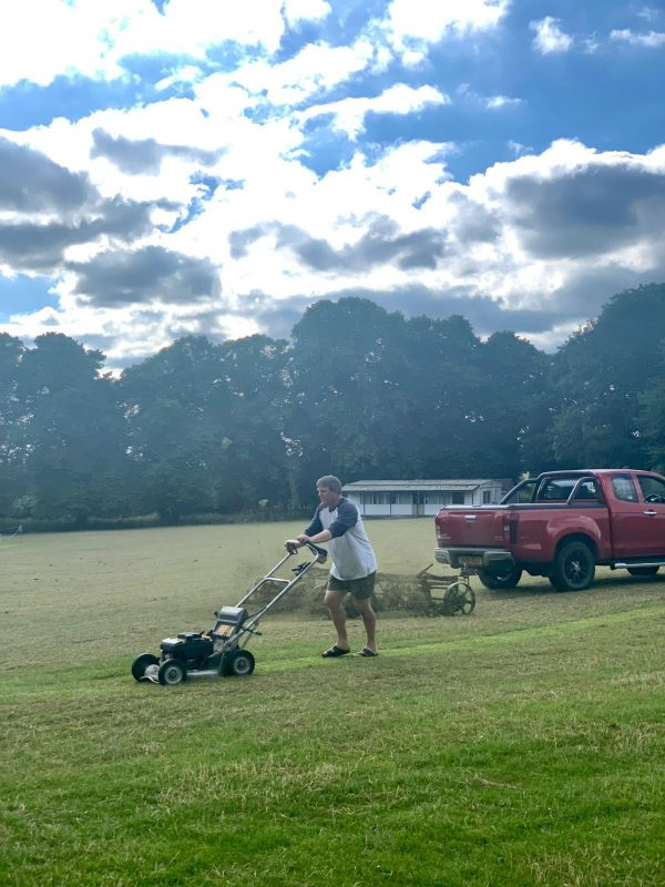 Getting the pitch ready for this evening's game of village cricket on the Oval